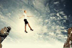 Image of pretty businesswoman balancing on rope