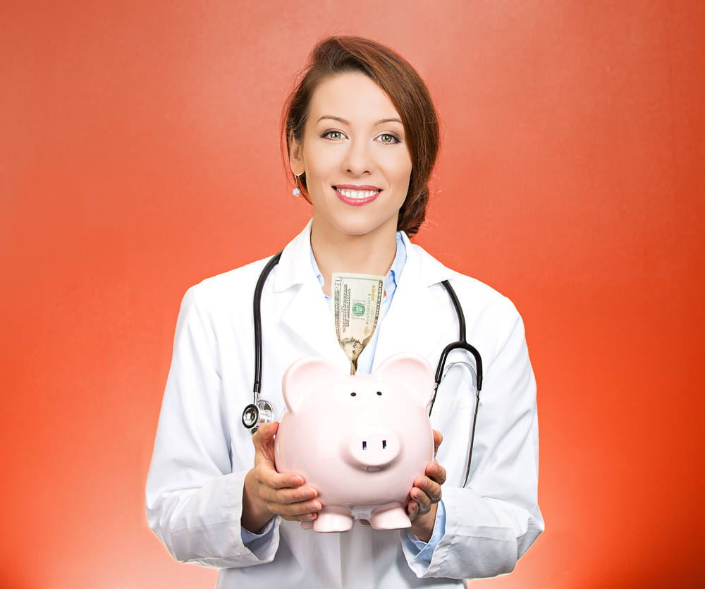 Closeup portrait female health care professional, doctor, nurse with stethoscope holding piggy bank, dollar bill, isolated red background. Medical insurance, medicare reimbursement, reform concept