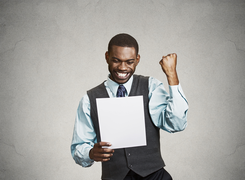 excited man holding a white piece of paper