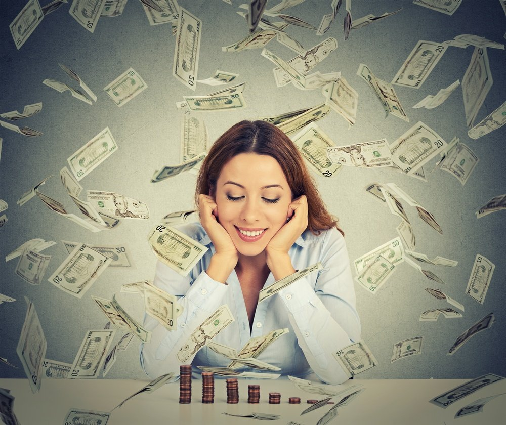 Excited happy young woman sitting at table with growing stack of coins under a money rain isolated on gray wall background. Positive emotions financial success luck good economy concept