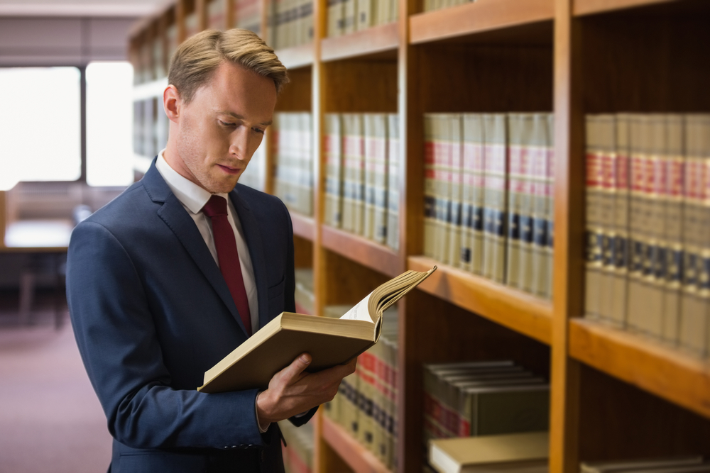 man in library reviewing law textbooks