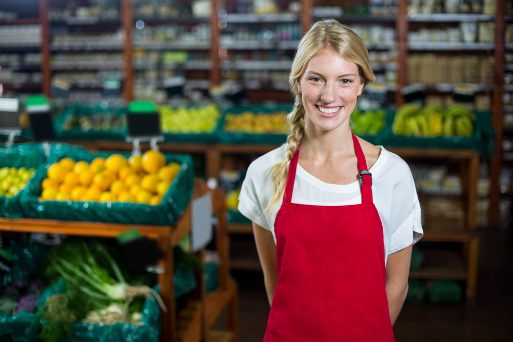 Portrait of smiling female staff standing in organic section of supermarket