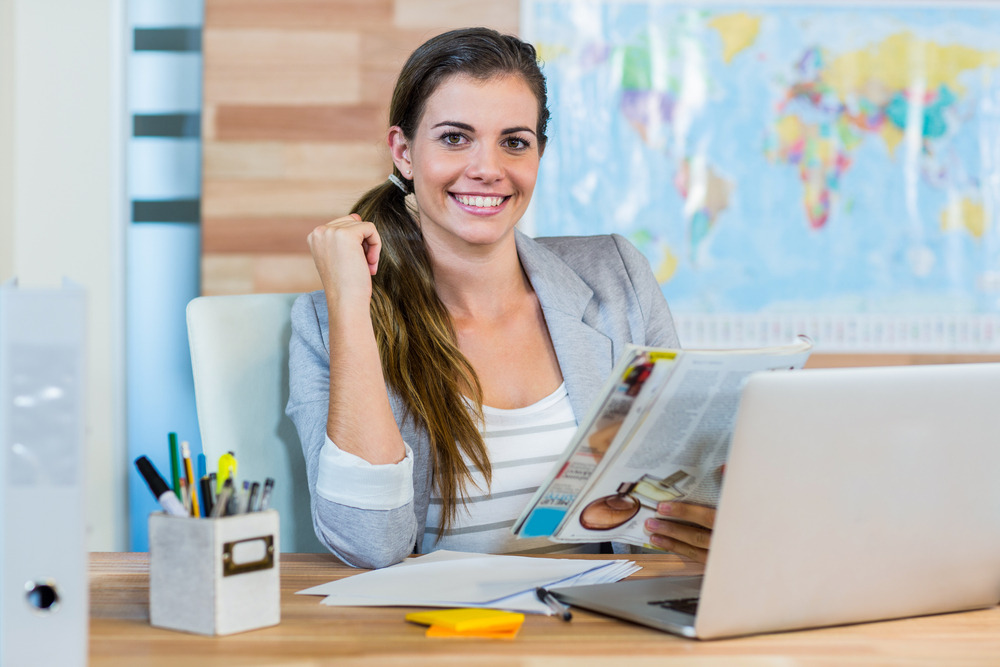 business woman sitting behind her laptop, at her desk holding documents