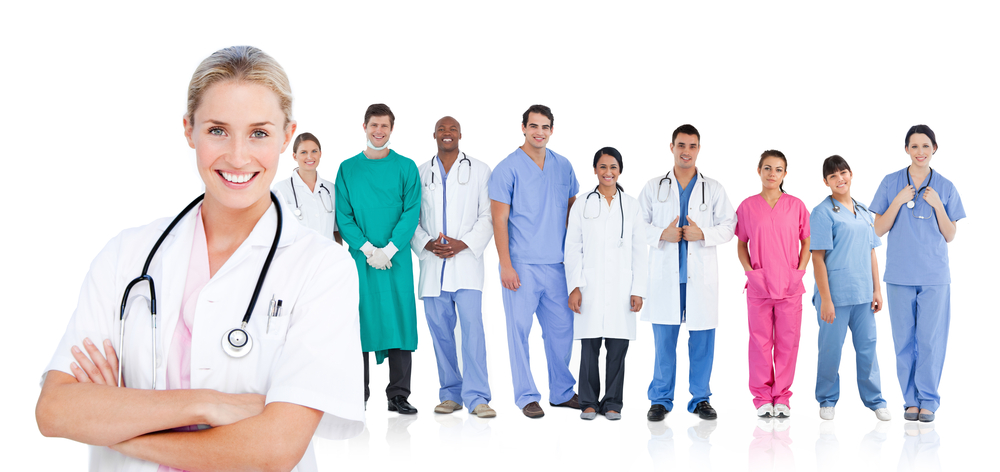 Smiling doctor standing in front of her medical team in line on white background