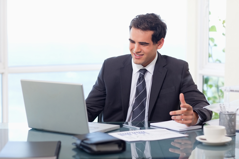 man sitting at desk with laptop